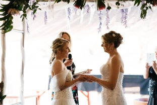 Tracy and Kim exchanging rings - photo by Kelly Harwood Photography